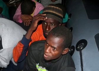 Illegal migrants who were trying to reach Europe are seen on a Libyan navy boat after being detained as they head towards the coastal city of Tripoli