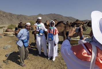 Indonesian pilgrims take photos with camels at a camel farm in Mecca