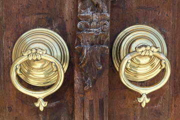 Closeup of two antique copper ornate door knockers over an aged wooden ornate door, Fatih Mosque, Istanbul, Turkey