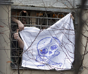Inmates hold a banner with a skull and crossbones from their cell window during a protest in Moscow