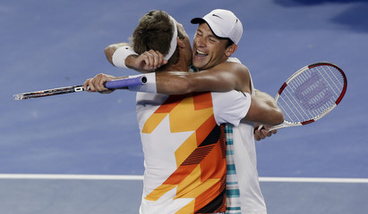 Lindstedt of Sweden hugs his partner Kubot of Poland after winning their men's doubles final match against Butorac of the U.S. and Klaasen of South Africa at the Australian Open 2014 tennis tournament in Melbourne