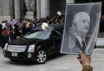 A man shows a picture of renowned Mexican author Carlos Fuentes, as a hearse carrying his coffin leaves after a tribute at the Bellas Artes Palace in Mexico City