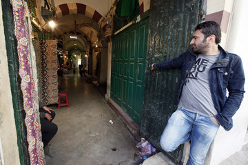 A man stands beside his shop waiting for customers in the old city of Tripoli