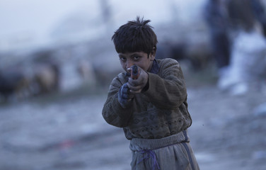 A young garbage collector plays with a toy a gun at a garbage dump on the outskirts of Kabul