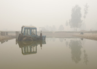An abandoned tractor is seen amidst heavy smog in the village of Kriusha