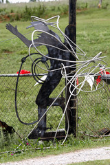 Wire cable is pictured wrapped around a sculpture of a cowboy silhouette after Tuesday's tornado which hit the town of Chickasha