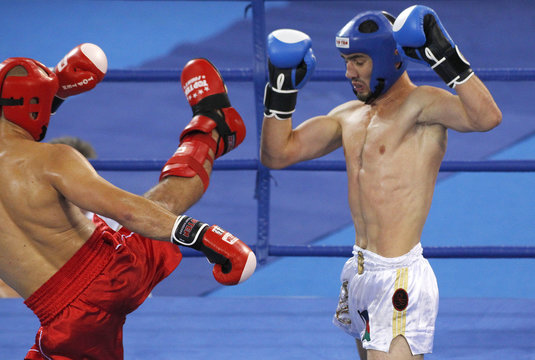 Parviz Abdullayev of Azerbaijan avoids a kick by Tomasz Mordarski of Poland during their semi-final bout in the low-kick 71kg kickboxing competition at the Combat Games in Beijing