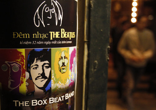 A fan walks near a poster promoting a tribute concert which marks the 32nd death anniversary of British legendary rocker Lennon of the Beatles at a vintage cafe in Hanoi