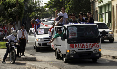 Paraguayan importers of used cars from Japan protest by using their trucks to block a major road leading into Asuncion