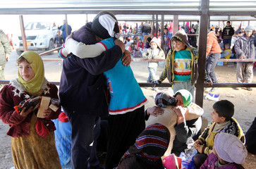 Displaced Iraqis from Hawijah area, who are fleeing from Islamic State militants, hug as they meet for the first time since they fled Hawijah, in Kirkuk