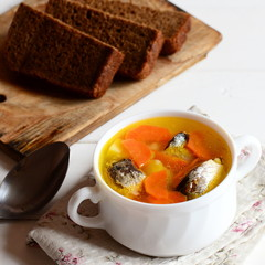 Quick, easy and delicious fish soup recipe. Homemade fish soup with potatoes and carrots in a bowl. Rye bread pieces on white wooden table. Closeup