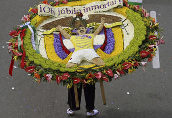 Man wears a floral arrangement bearing the image of Colombian national soccer player James Rodriguez, takes part in the annual flower parade in Medellin