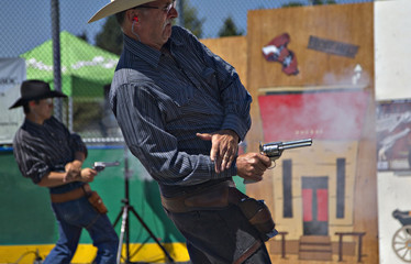 Lawton of Deadwood, South Dakota, fires his single action revolver after cocking the gun with his left hand during the Canadian Open Fast Draw Championships in Aldergrove