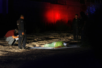 The body of a woman with her head bound in grey tape lies in an alley in Ciudad Juarez