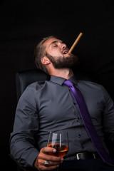 Portrait eines jungen relaxenden Geschäftsmannes mit Getränk und Zigarre