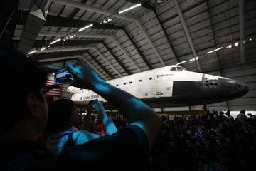 Visitors take photos during opening day of the Space Shuttle Endeavour Exhibition in Los Angeles