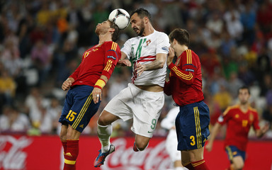 Portugal's Almeida jumps for header with Spain's Ramos and Pique during Euro 2012 semi-final soccer match in Donetsk