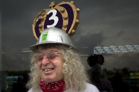 A spectator wears a hard hat with a triple crown logo in the rain in the general admission area before the running of the 147th Belmont Stakes in Elmont