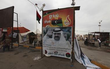 Libyans sit next to a poster of Qatar's Emir Sheikh Hamad bin Khalifa al-Thani near the court house in Benghazi