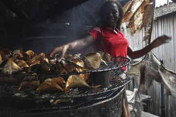 A woman smokes fish in a local kitchen in the Makoko fishing community in Nigeria's commercial capital Lagos