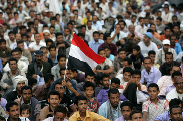A boy waves Yemen's national flag during a sit-in by anti-government protesters demanding the ouster of Yemen's President Ali Abdullah Saleh in Taiz