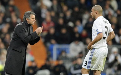 Real Madrid's coach Jose Mourinho gives instructions to Pepe during their Spanish first division soccer match against Atletico Madrid in Madrid