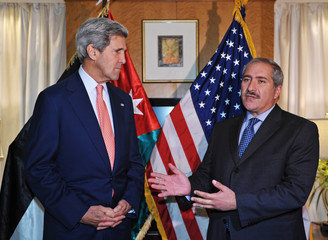 U.S. Secretary of State Kerry listens to Jordanian FM Judeh during a meeting at a hotel in Amman