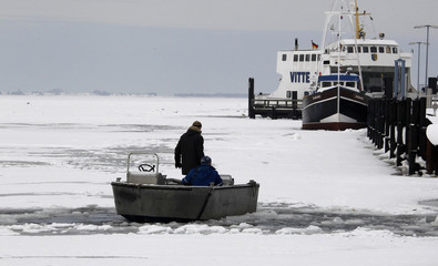 A boat makes its way through the frozen Baltic sea in the harbour of Schaprode on Ruegen island