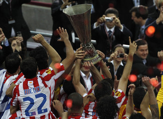 Atletico Madrid players celebrate with trophy after defeating Athletic Bilbao to win Europa League final soccer match in Bucharest