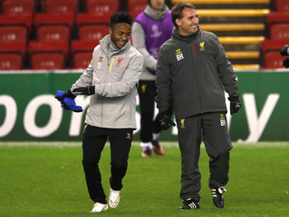 Liverpool's manager Rodgers laughs with Sterling during a training session at Anfield in Liverpool