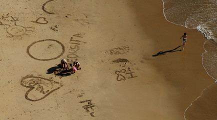 People make drawings onto the sand of the Virgen de Regla beach in Chipiona, southern Spain