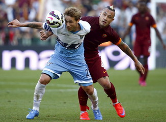 AS Roma's Nainggolan challenges Lazio's Biglia during their Serie A soccer match at the Olympic stadium in Rome
