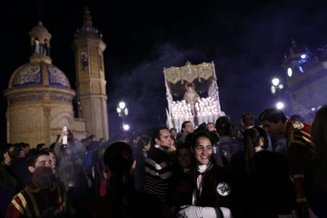 Members of the San Gonzalo brotherhood smile as they take part in a Holy Week procession in Seville