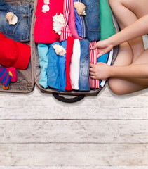 Woman packing luggage for a new journey on a wooden floor. Place for your text.