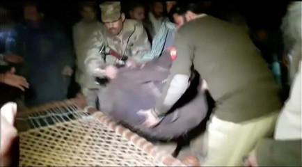 Army personnel and local residents move remains of victims during the rescue operation at a remote crash site where a plane carrying 47 people crashed into a northern Pakistan mountain, in this still frame taken from video