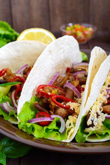 Tacos is a traditional Mexican dish. Tortilla stuffed with chicken, bell and hot peppers, beans, lettuce, cheese, blue onion with salsa sauce on dark wooden background. Vertical view