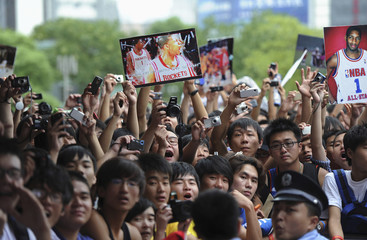 Chinese basketball fans display pictures of NBA basketball player Tracy McGrady during a promotional event of his China tour in Hefei