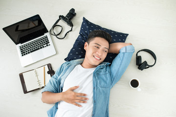 Top view of asian man lying on the floor with laptop, camera, tablet, coffee and phone