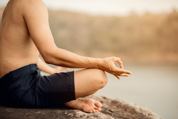 Young man is practicing yoga at mountain lake