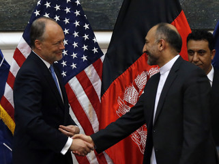 Afghan national security adviser Hanif Atmar and U.S. Ambassador James Cunningham shake hands after signing the bilateral security agreement in Kabul
