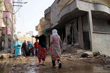 Turkish Kurdish women walk past a damaged building in the southeastern town of Cizre in Sirnak province, Turkey