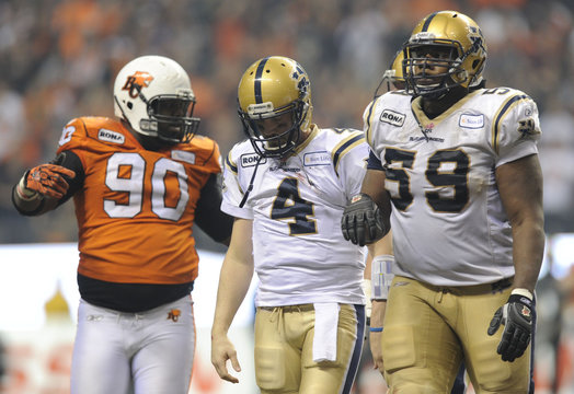 Winnipeg Blue Bombers quarterback Pierce walks off the field with teammate Douglas next to BC Lions' Hunt after a series of downs in the second half of the CFL's 99th Grey Cup football game in Vancouver