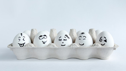 Eggs with funny faces in the package on a white background. Easter Concept Photo. Faces on the eggs