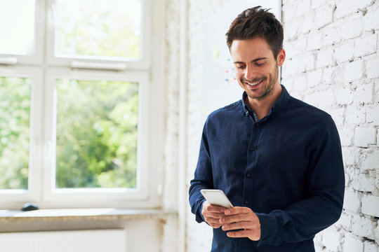 Happy young man using his smartphone at office