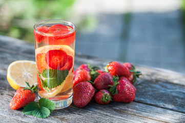 A glass of  detox water. Strawberry, lemon and mint with cool clean water, backdrop of a green garden. Detox, diet, Cookery, sports, proper nutrition, sports nutrition, body cleansing