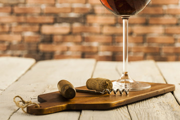 Wine glass and bottle on a wooden table with bricks wall background