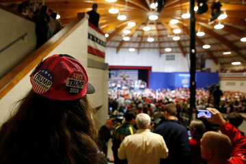 A girl sits on her father's shoulders at the back of a rally with Republican presidential nominee Donald Trump and his supporters in Waukesha, Wisconsin