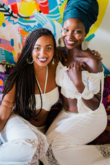 Young beautiful African female friends in white dress