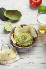 Homemade guacamole with corn nachos and a glasses of beer