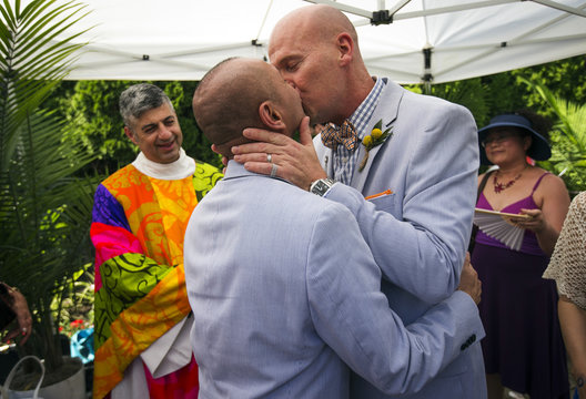 """Montenegro and Allen kiss in their private ceremony after """"The Celebration of Love"""" grand wedding where over 100 LGBT couples got married at Casa Loma in Toronto"""